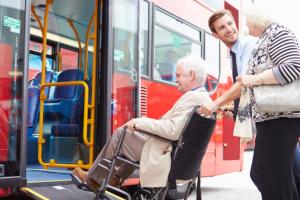 man assisting elderly man on a wheelchair