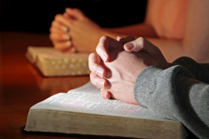 hands of the persons praying